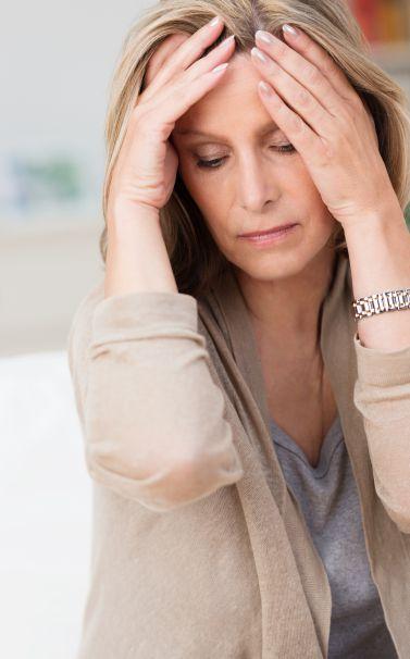 Donna preoccupata che si tiene la testa con le mani | Daflon® 500