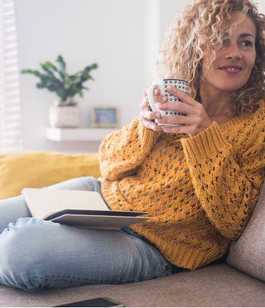 Donna seduta sul divano con una tazza in mano | Daflon® 500