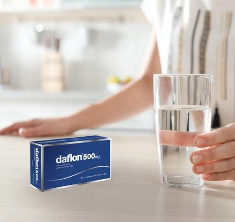 Daflon® 500 confezione su tavolo accanto a bicchiere d'acqua