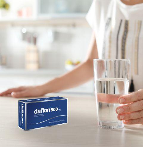 Donna che tiene un bicchiere d'acqua su un tavolo con accanto confezione di Daflon® 500