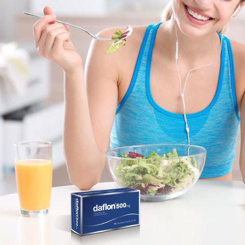 Donna sorridente che mangia insalata da una ciotola, confezione di Daflon® 500 e bicchiere di succo di frutta sul tavolo