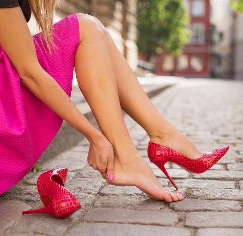 Donna seduta su marciapiede che si massaggia i piedi | Daflon® 500