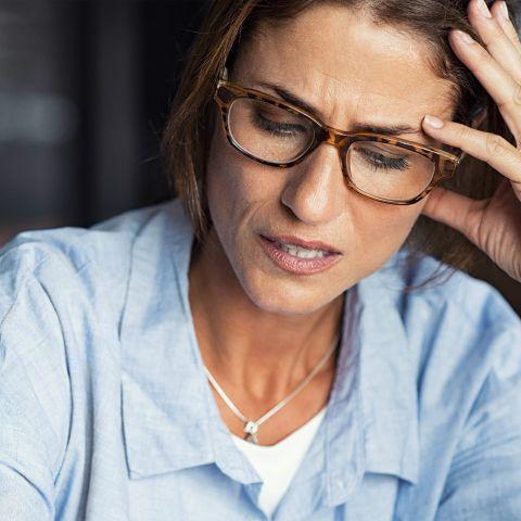 Donna sofferente che si regge la testa Emorroidi