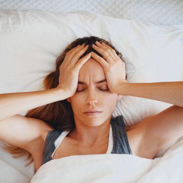 Donna sofferente sdraiata che si regge la testa | Daflon® 500