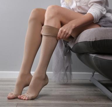 Donna seduta su poltrona che si sistema le calze