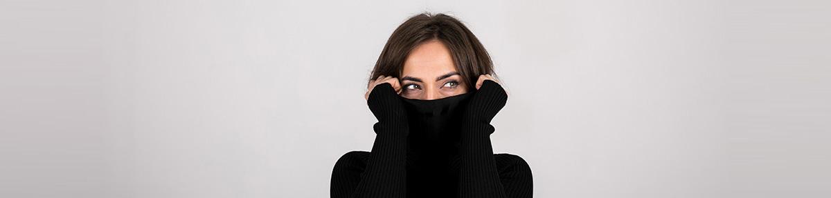Primo piano di donna con maglione nero che si tiene la testa tra le mani | Daflon® 500