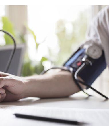 Braccio maschile appoggiato su tavolo con misuratore di pressione | Daflon® 500
