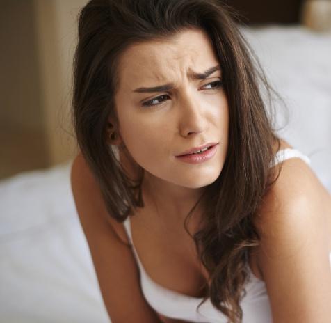 Donna con faccia sofferente per le complicazioni dell'insufficienza venosa